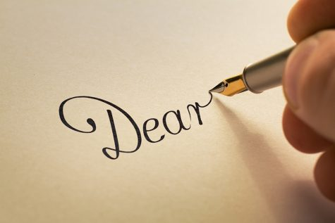 Hand is writing calligraphic letter starting with dear using old pen on yellow paper